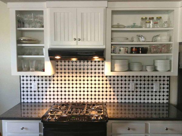 Cozinha com decoração branca e preta, armários, fogão e um depurador de ar acima do fogão.
