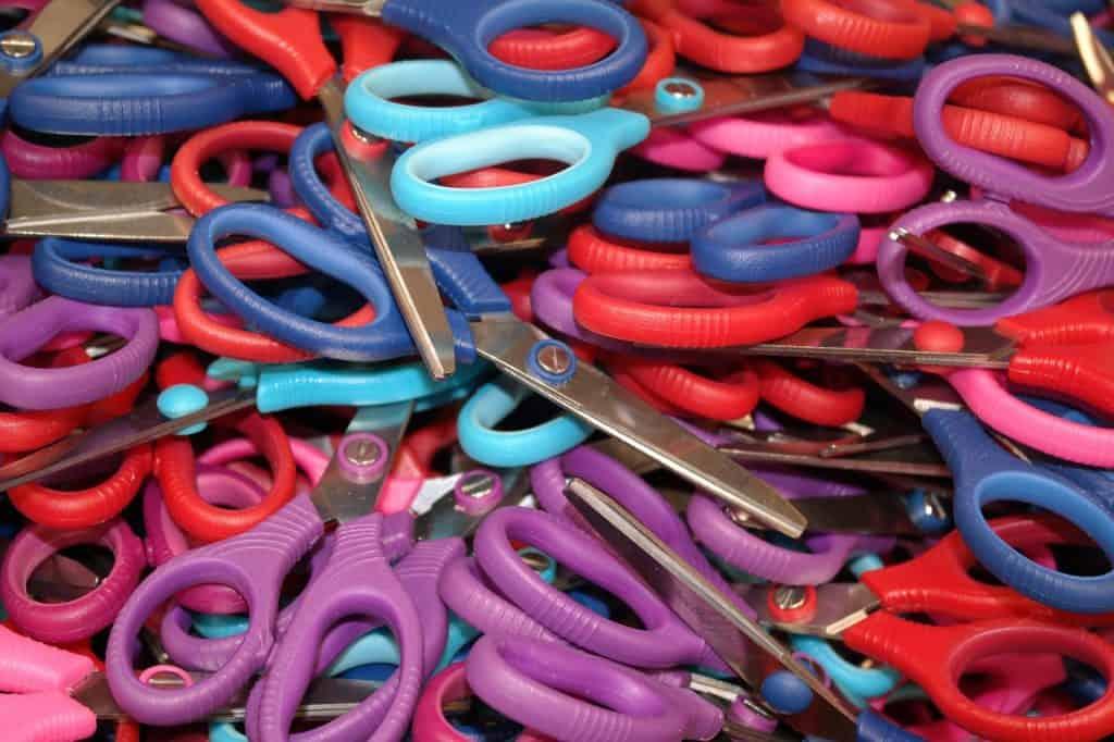 Imagem mostra pilha de tesouras escolares coloridas.