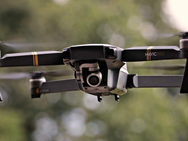 Imagem mostra um drone quadricóptero em voo.