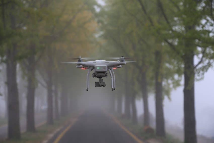 Imagem mostra um drone quadricóptero fazendo uma filmagem em meio a árvores.