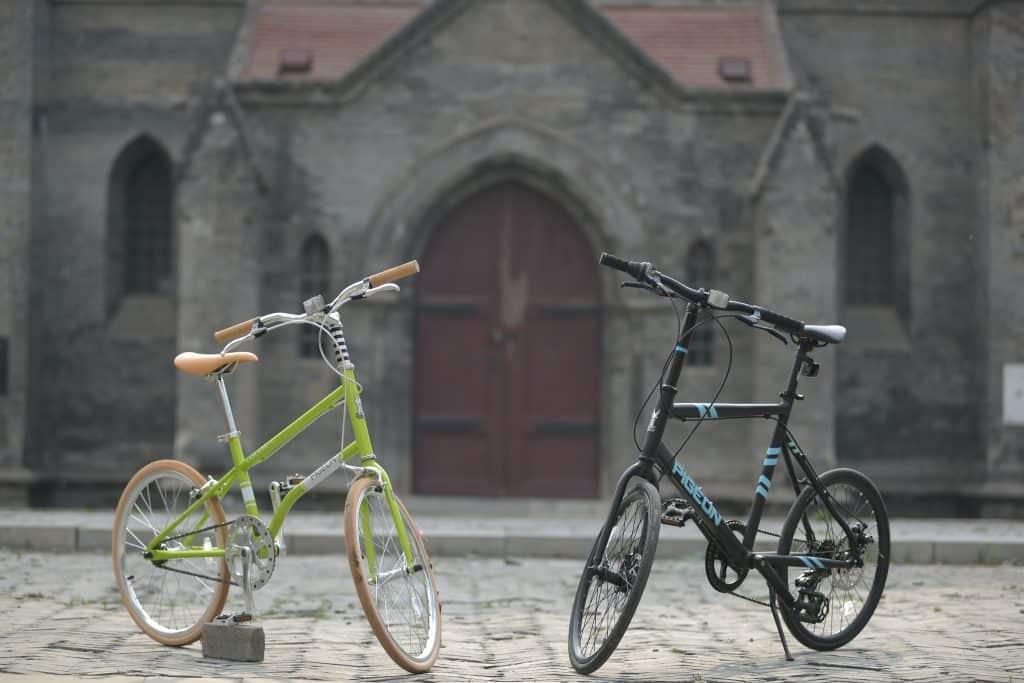 Imagem mostra em primeiro plano, uma bicicleta colorida, à esquerda, e uma preta, à direita. Ao fundo, a porta de uma igreja antiga.