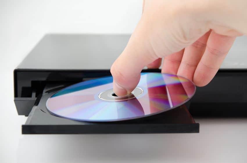 Mão inserindo DVD dentro de aparelho.