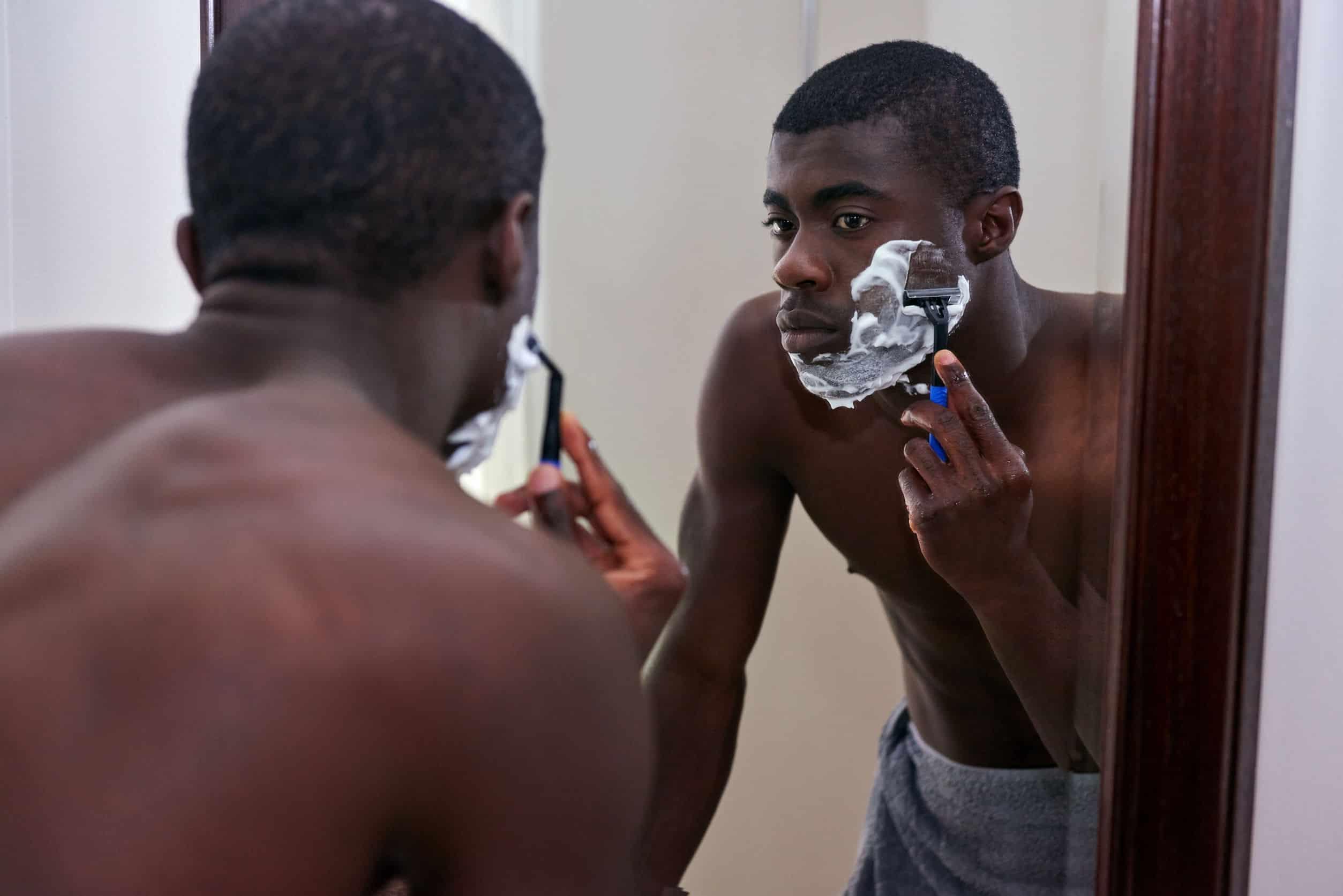 Imagem mostra homem se barbeando, com uma lâmina no lado direito do rosto cheio de espuma de barbear.