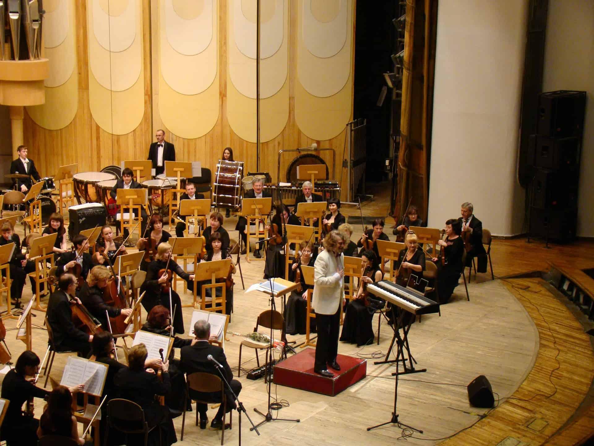 A imagem mostra uma orquestra. Todos os músicos estão sentados na frente de uma estante para partitura.