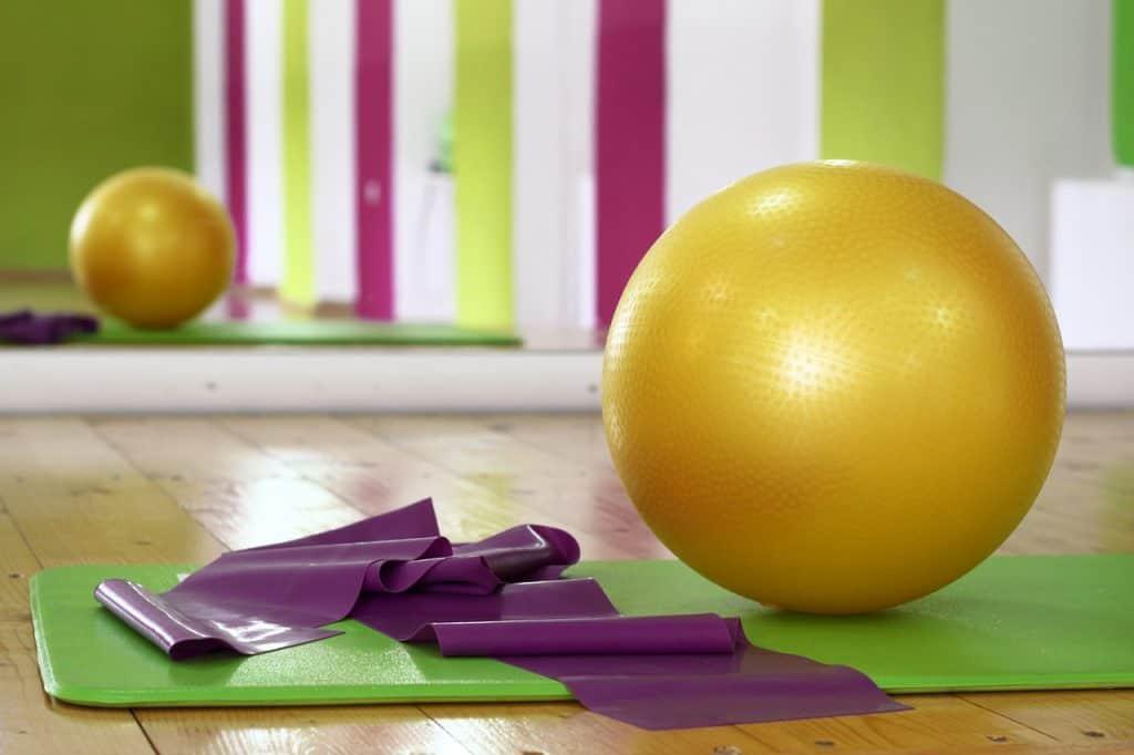 Colchonete de academia com faixa de alongamento e bola de pilates.