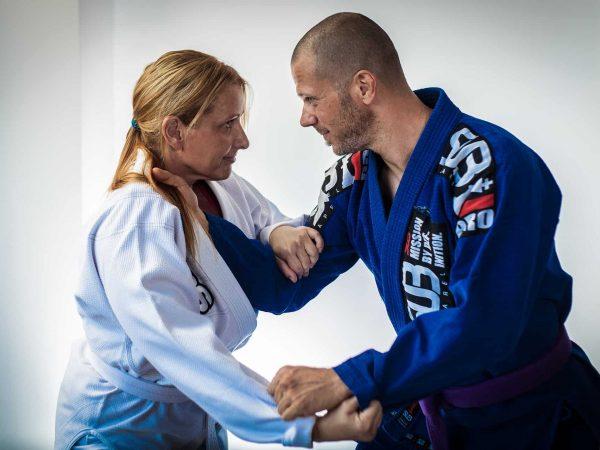 Imagem mostra um homem e uma mulher lutando jiu-jitsu.