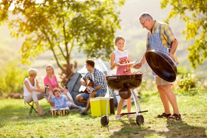 Homem prepara churrasco em um gramado junto com uma garotinha durante acampamento de família.