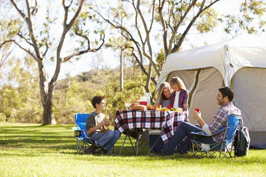 Família sentada à mesa comendo em um acampamento com barraca e tenda ao fundo.