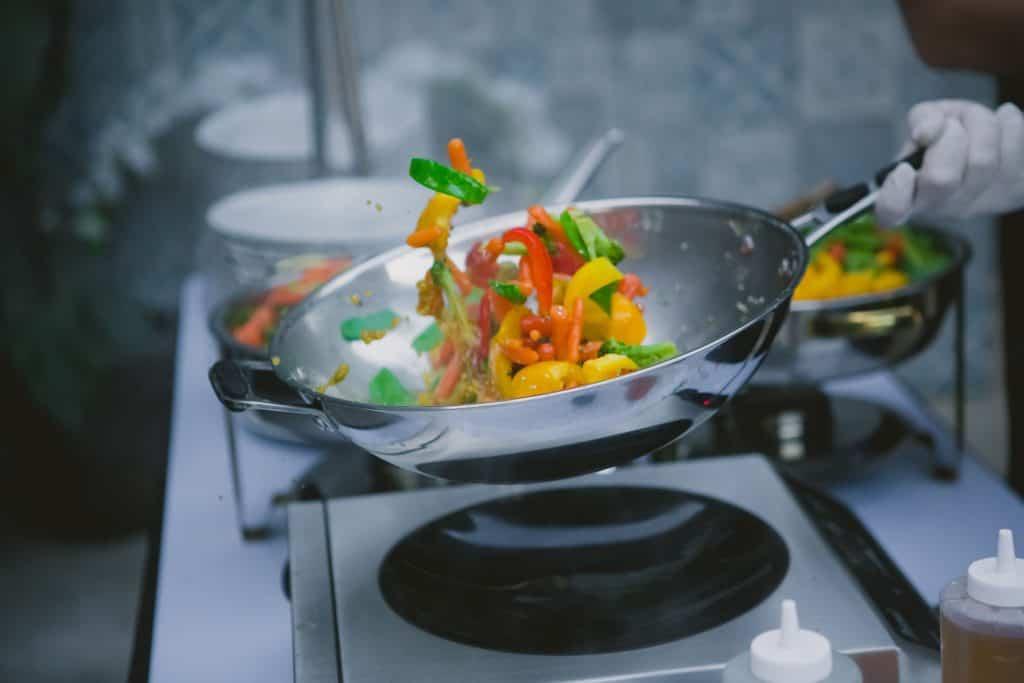 Imagem de panela wok com legumes dentro sendo preparados.
