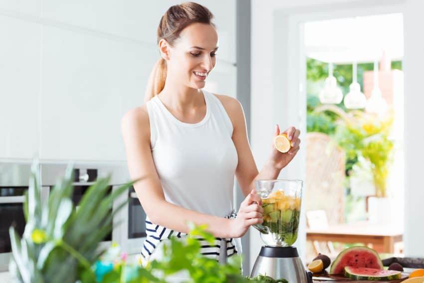 Mulher preparando suco verde com um liquidificador.