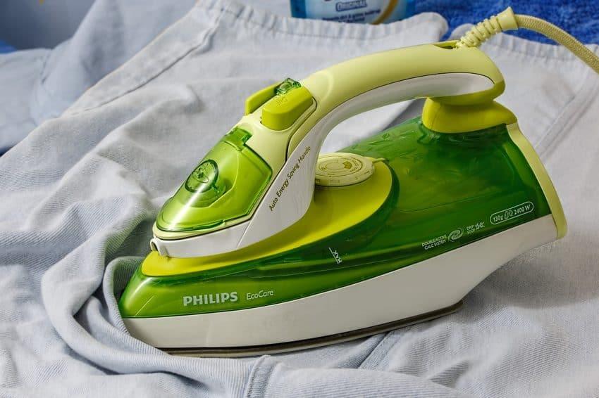 Imagem mostra um ferro de passar roupa verde em cima de uma roupa.