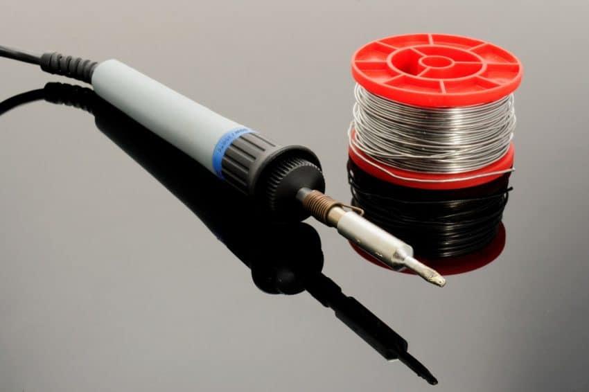 Imagem de um ferro de solda com rolo de estanho, para soldagem.