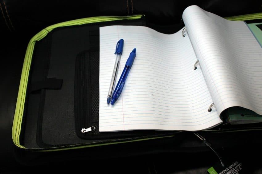 Fichário escolar aberto com papel e caneta.