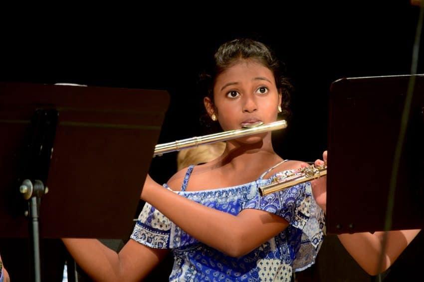 Uma menina está olhando para o horizonte e tocando flauta transversal. Há duas estantes para partitura na frente dela.