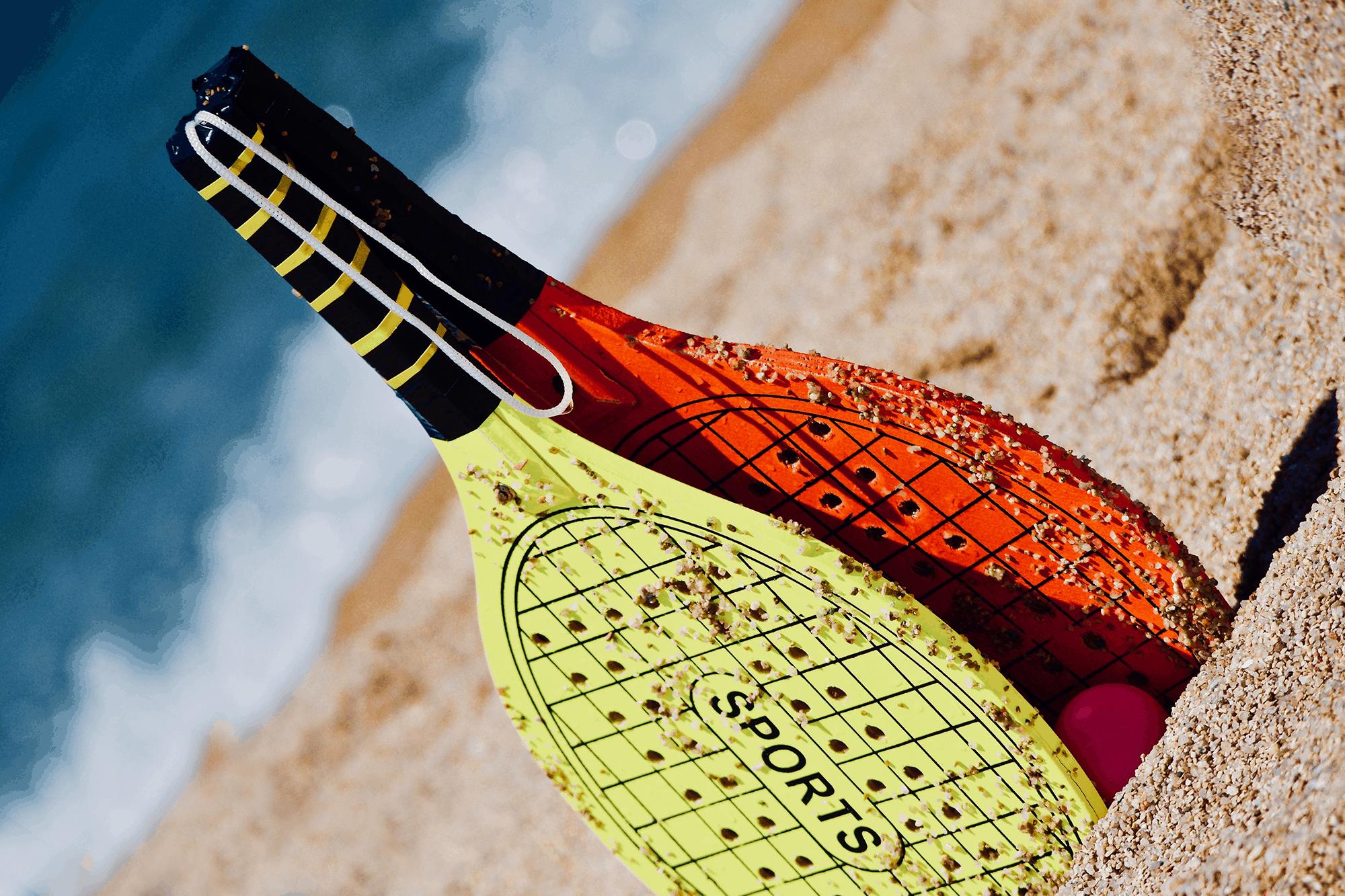 Imagem de par de raquetes coloridas com bolinha em praia com mar ao fundo.