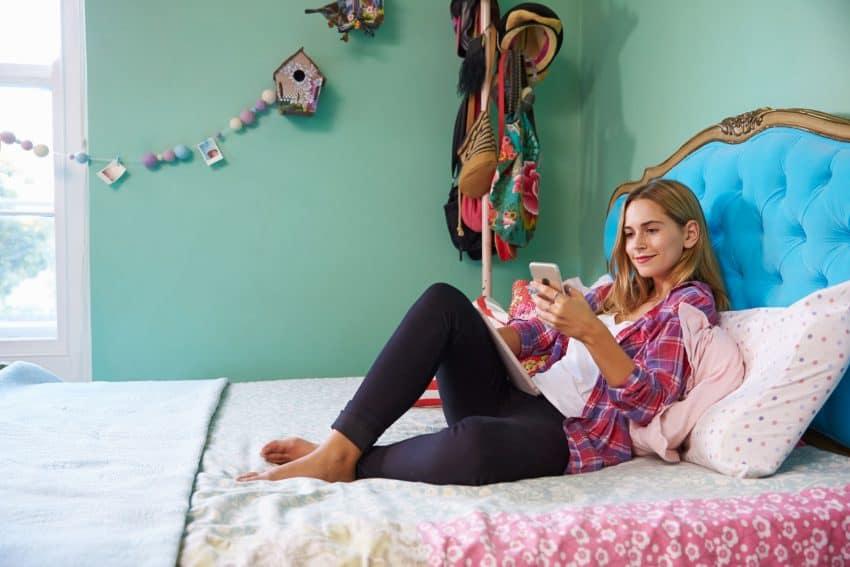Imagem de uma garota mexendo no celular na cama de casal e cabeceira azul.