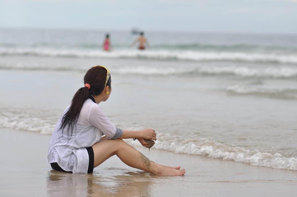 Uma menina com camiseta UV sentada na beira do mar com um pouco de areia molhada nas mãos.