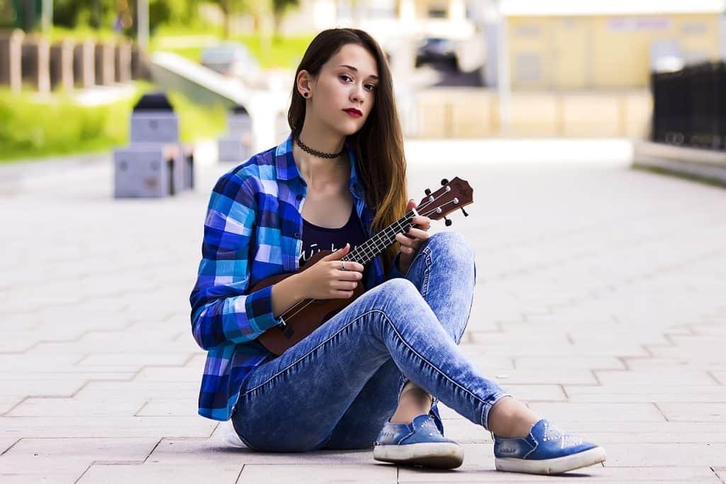 Imagem de garota sentada no chão tocando ukulele.