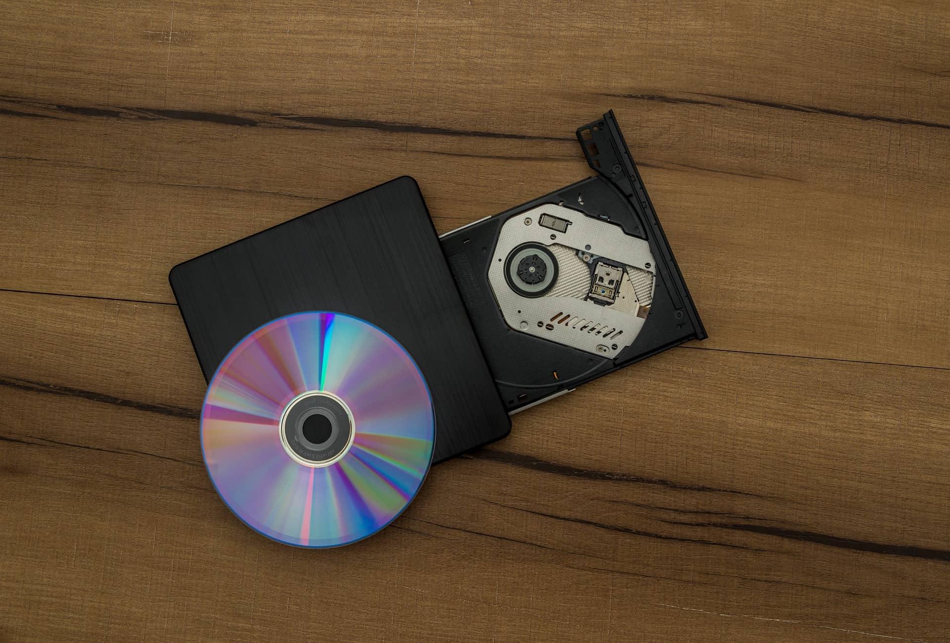 Imagem de um gravador de DVD aberto com um disco sobre o aparelho.
