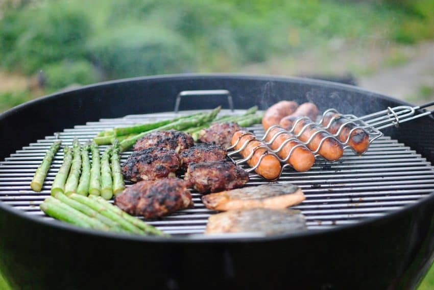 Imagem de uma churrasqueira assando carnes, linguiças, peixes e aspargos.
