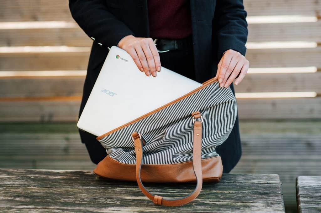Imagem de uma mulher colocando um chromebook dentro da bolsa.