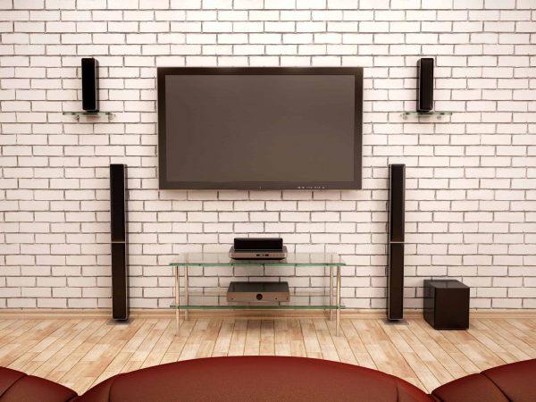Sala de estar com tijolinhos à vista brancos com tv e home theater.