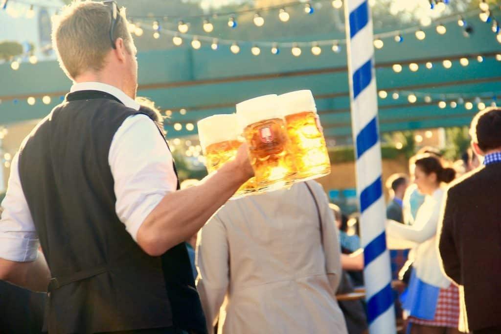 Fotografia de uma festa, onde há um homem carregando quatro canecos com um litro de chopp para servir.