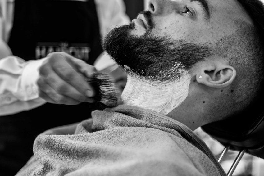 Imagem mostra um barbeiro espalhando creme de barbear no pescoço de um homem, logo abaixo de sua barba.