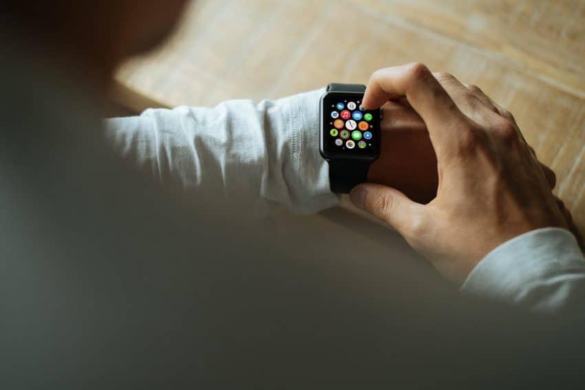 Imagem de um smartwatch preto no pulso de um homem.