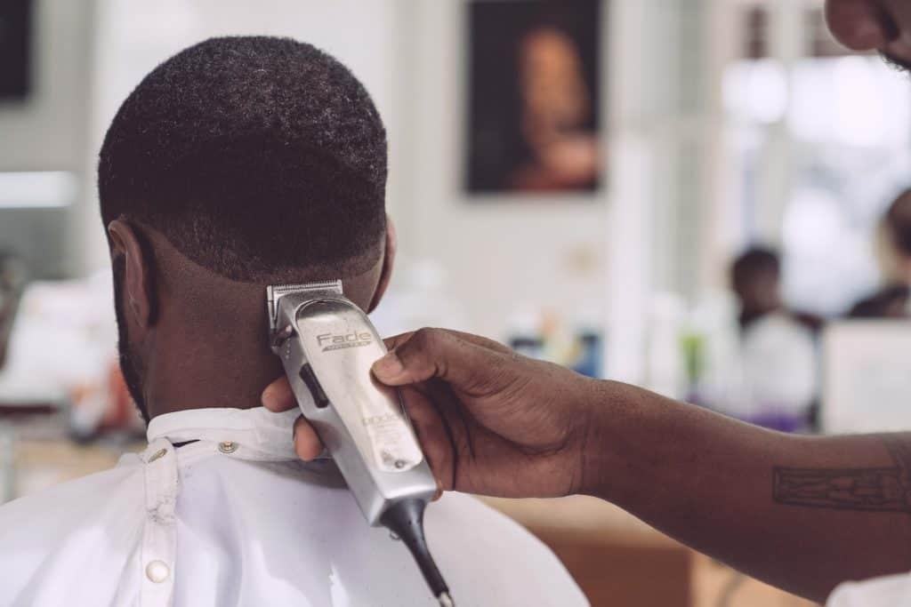 Imagem mostra a mão de uma pessoa segurando uma máquina de cortar cabelo e utilizando o aparelho para aparar os cabelos de outra pessoa.