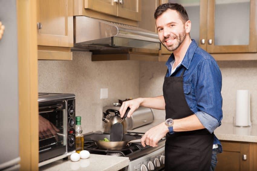 Homem sorrindo usando avental fritando ovos em uma cozinha pequena.