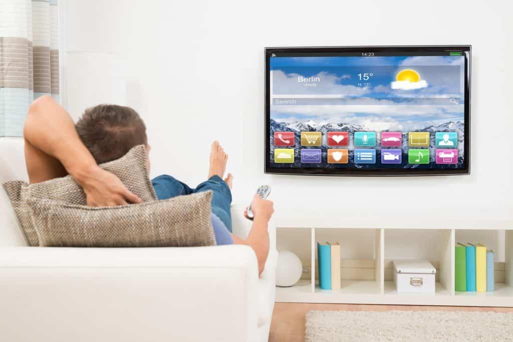 Imagem de um homem deitado no sofá mexendo no controle remoto da smart tv.