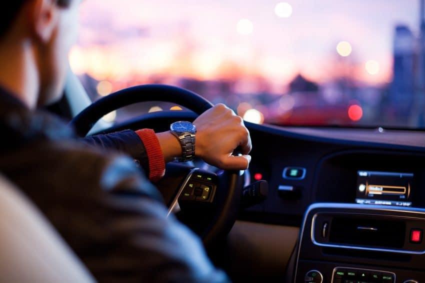 Imagem mostra um homem dirigindo um carro com o rádio ligado.