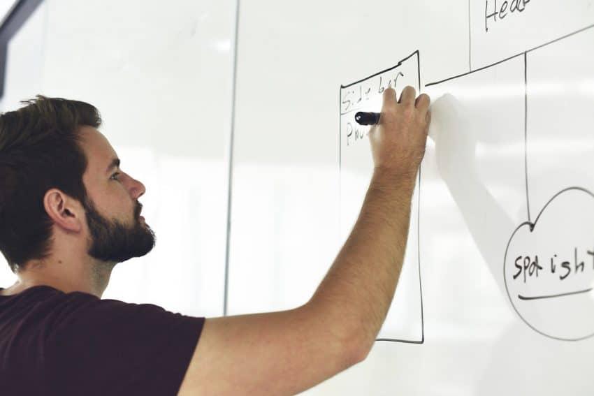 Homem escrevendo em quadro magnético branco.