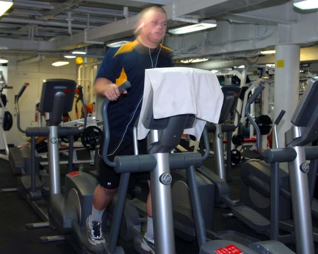 Homem utilizando um aparelho elíptico durante exercícios em academia.