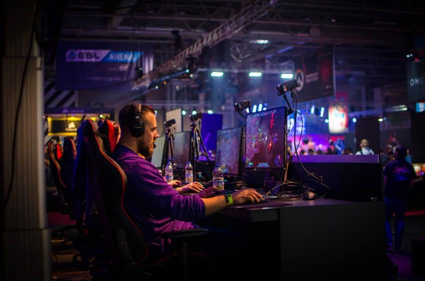 Image shows a man in front of a monitor playing on a PC gamer.