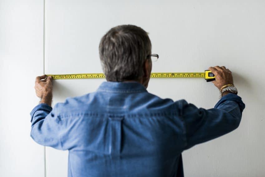 Imagem de uma homem utilizando uma trena para calcular o comprimento de uma parede.