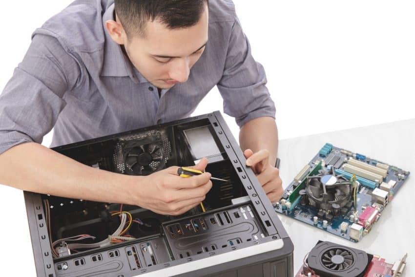 Homem mexendo no interior de um computador com uma chave.