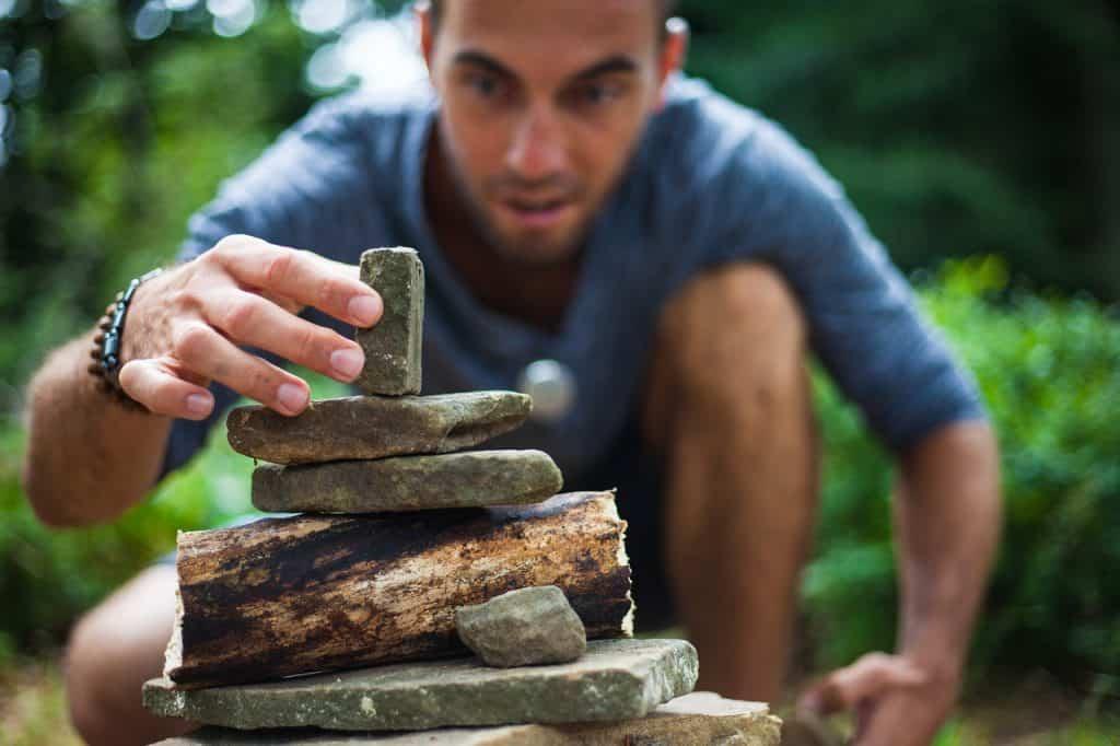 Um homem trajando uma camiseta UV fazendo esculturas com pedras pequenas na natureza.
