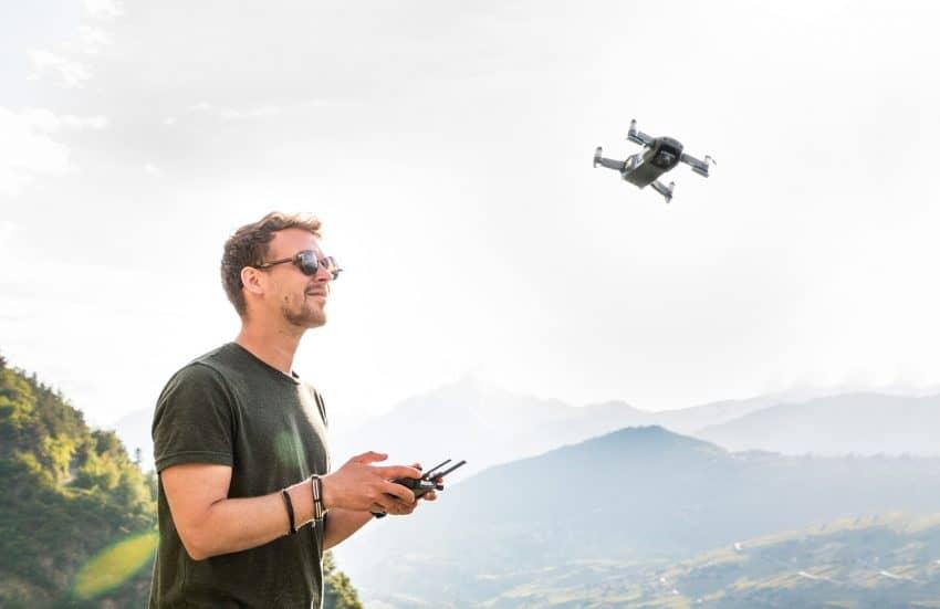 Homem pilotando um drone em um lugar montanhoso em um lindo dia de sol.