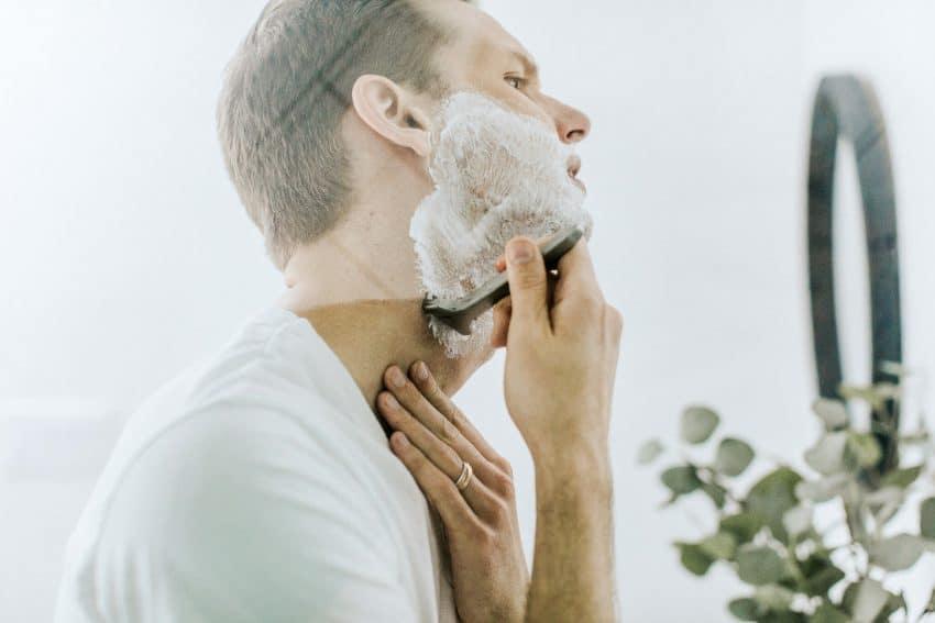 Imagem mostra um homem se barbeando. Sua mão direita raspa a barba com a lâmina, enquanto sua mão esquerda garante a tensão da pele.
