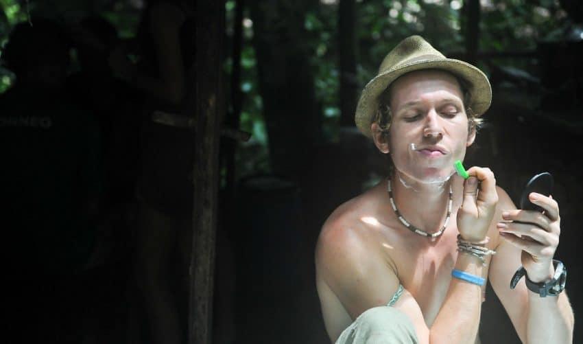 Imagem mostra um homem se barbeando em frente a um pequeno espelho de mão, que carrega na sua direita; com a esquerda, finalizada a raspagem.