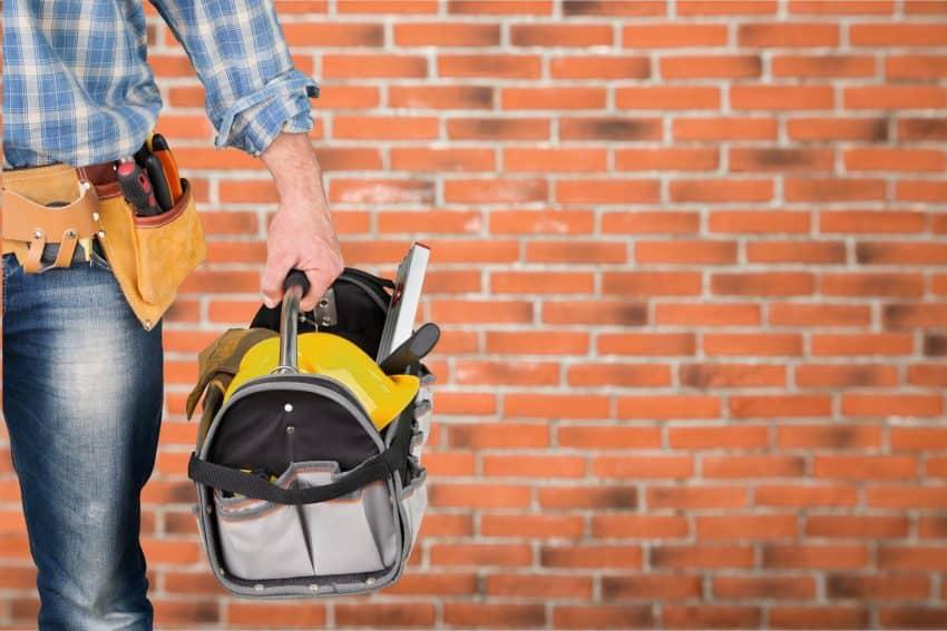 Parte do corpo de um homem segurando uma caixa de ferramentas com parede de tijolinho nos fundos.