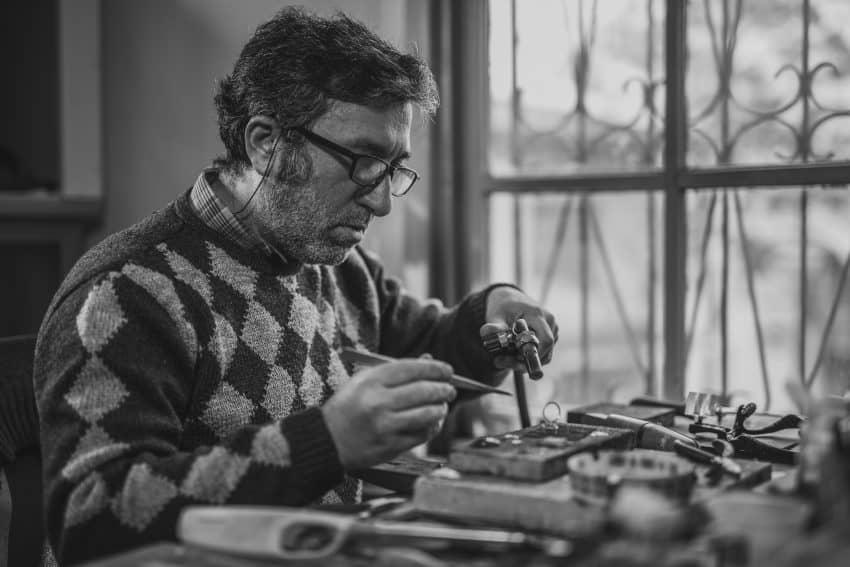 Imagem mostra um homem usando óculos trabalhando num projeto. Ele carrega um maçarico na mão esquerda e uma pinça na mão direita. Em segundo plano, mais ferramentas, desfocadas.