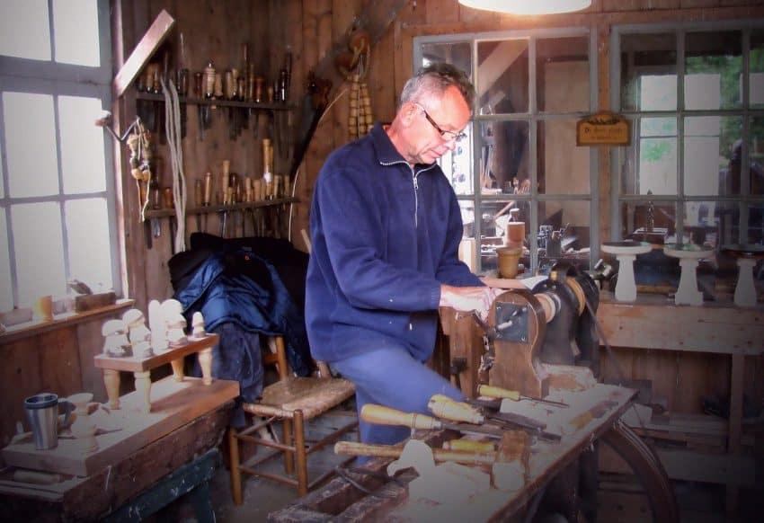 Imagem mostra um homem sentado fazendo trabalhos em madeira.