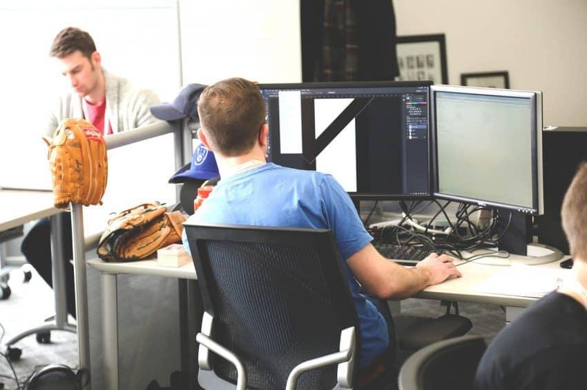 Homem de costas sentado na frente de uma escrivaninha olhando para um computador com duas telas.