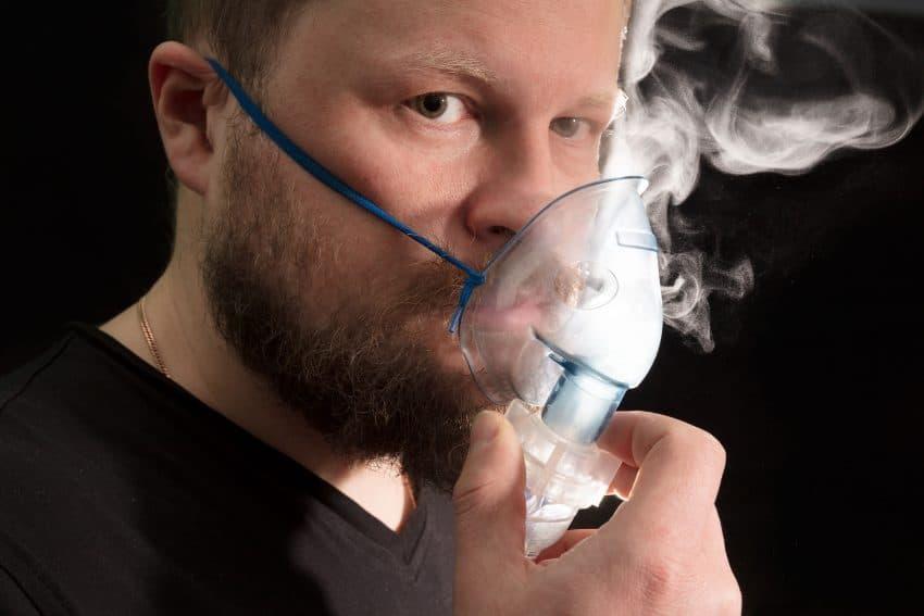 Imagem de homem usando nebulizador com bastante névoa.