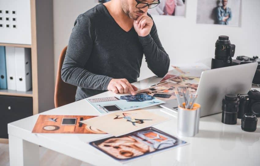 Imagem de homem em frente a um computador com várias fotos impressas.