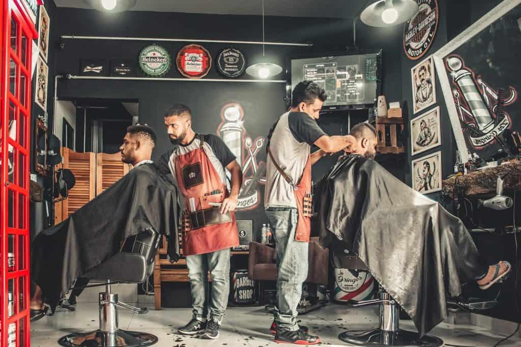 Imagem de barbearia com dois homens sentados em cadeiras e dois homens cortando seus cabelos.