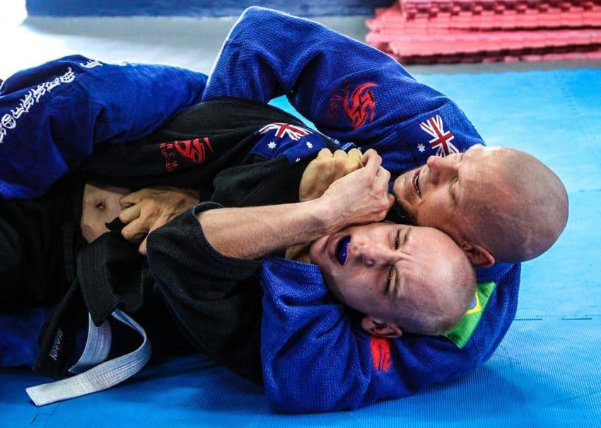 Dois homens lutam jiu-jitsu em um tatame azul.